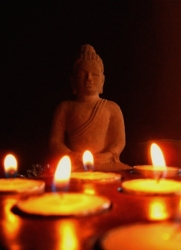 Statue of Buddha with candles