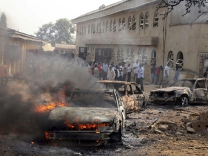 A car burns at the scene of a bomb explosion at St. Theresa Catholic Church at Madalla, Suleja, Nigeria