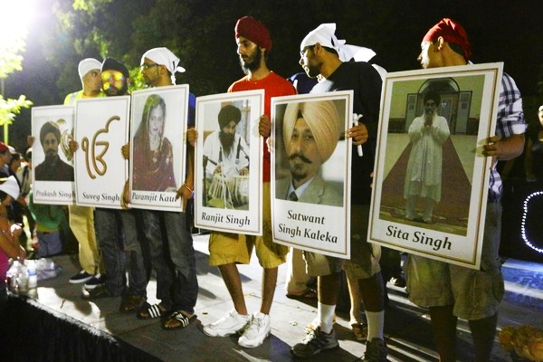 Sikhs hold up placards with photos of six mass shooting victims after a candlelight vigil Tuesday in Oak Cree