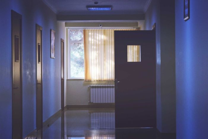 dimly lit hospital corridor with one door open