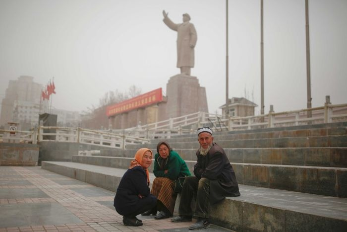 Uighers sit near a statue of Mao