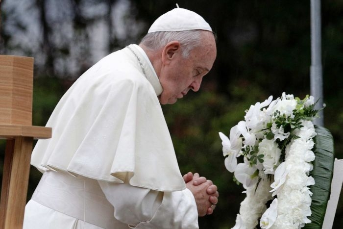 Pope Francis wearing papal robes bows his head, closes eyes, clasps hands in prayer in front of white wreath.