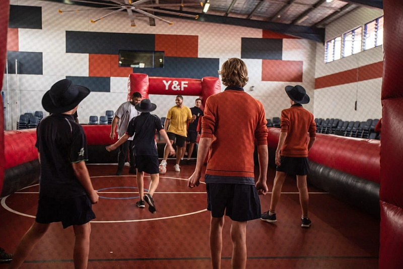 Youth pastors run a sports session at a school.