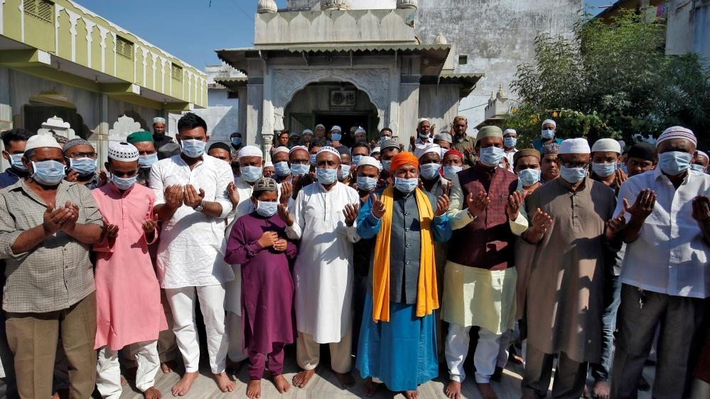 Muslims wearing masks pray for coronavirus patients