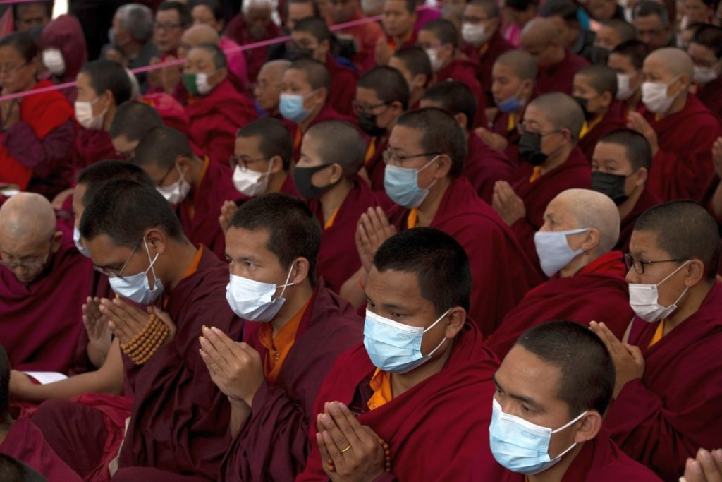 Tibetan monks at prayer - wearing masks