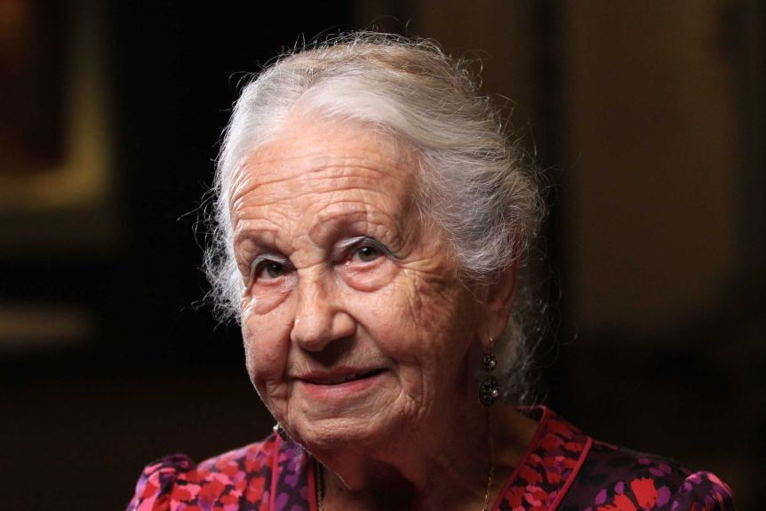 An old woman with white hair looks towards the camera.
