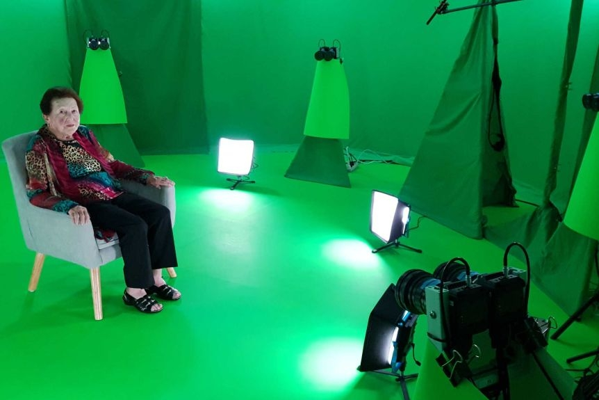 An old woman with brown hair sits in a room surrounded by green screens and cameras.