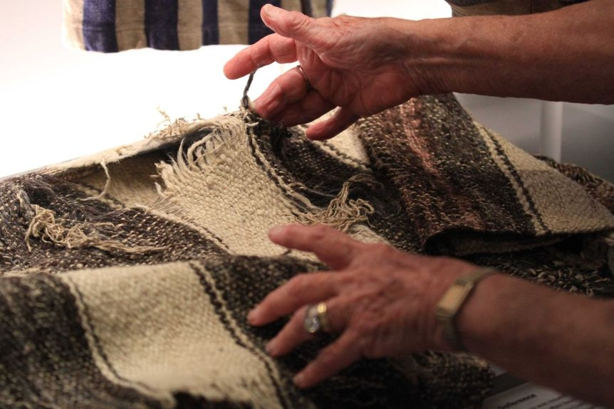 An older woman's hands can be seen gently touching a black and white woven blanket.