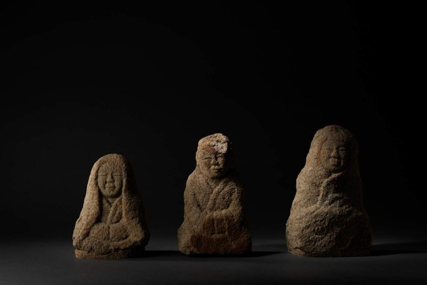 Row of three small human-shaped stone sculptures, sitting cross-legged in Buddhist poses.