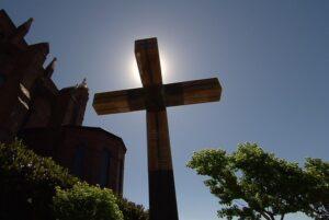 A crucifix stands outside a church.